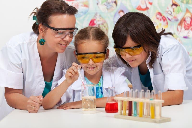 Niños en clase de química con su profesor fotos de archivo libres de regalías