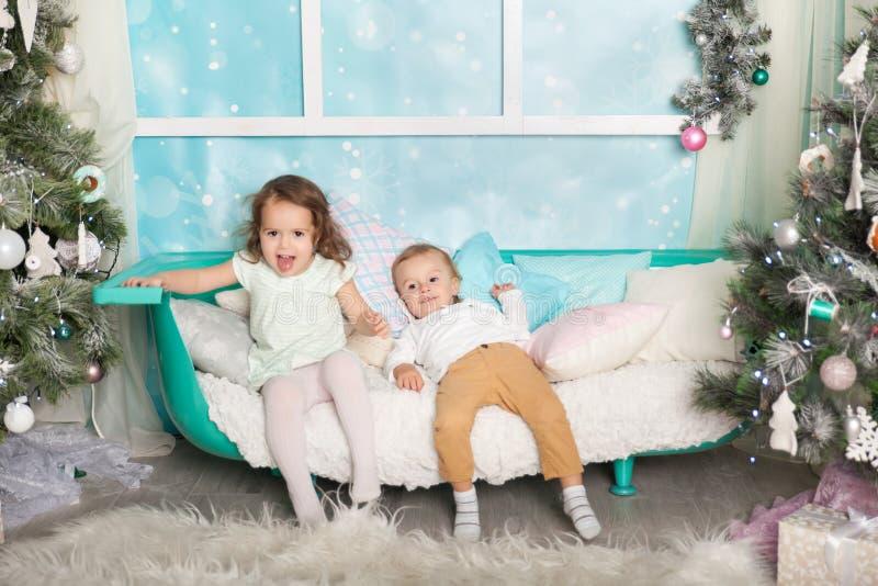 Niños en decoraciones de una Navidad fotografía de archivo