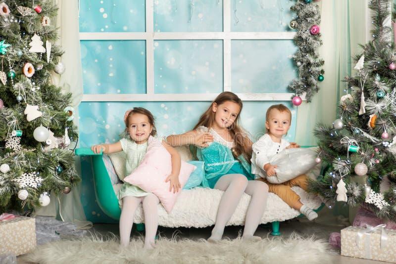 Niños en decoraciones de una Navidad foto de archivo