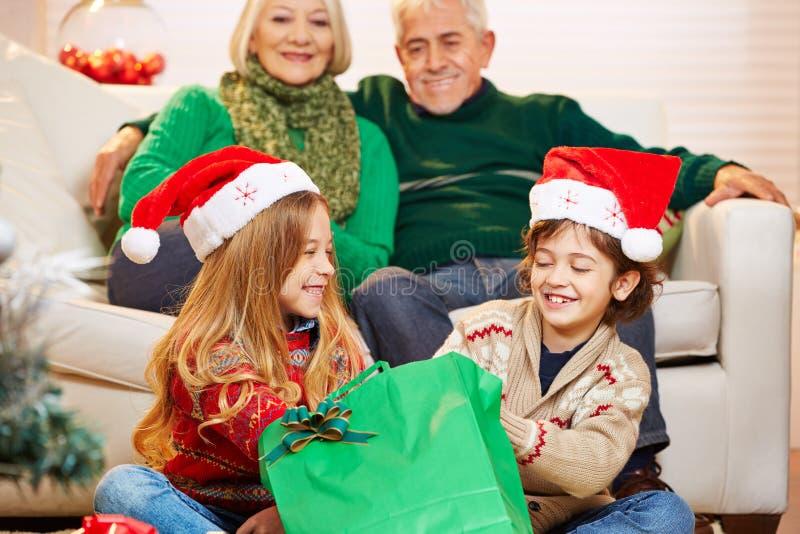 Niños en el abuelo y la abuela en la Navidad imagenes de archivo