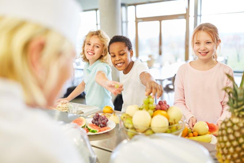 Niños en el buffet de la fruta de la cafetería imagen de archivo