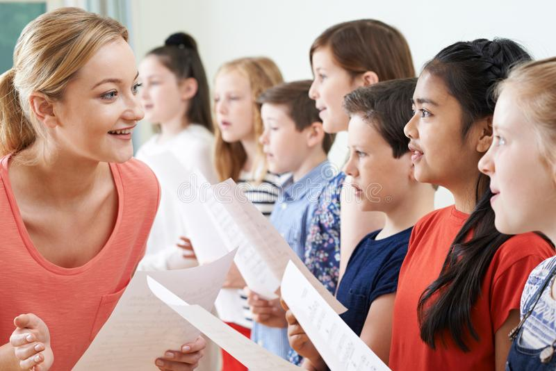Niños en el coro de escuela que es animado por el profesor imagen de archivo