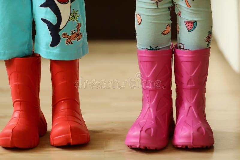 Niños en el desgaste colorido de los rainboots bastante fresco y los paraguas imagen de archivo libre de regalías