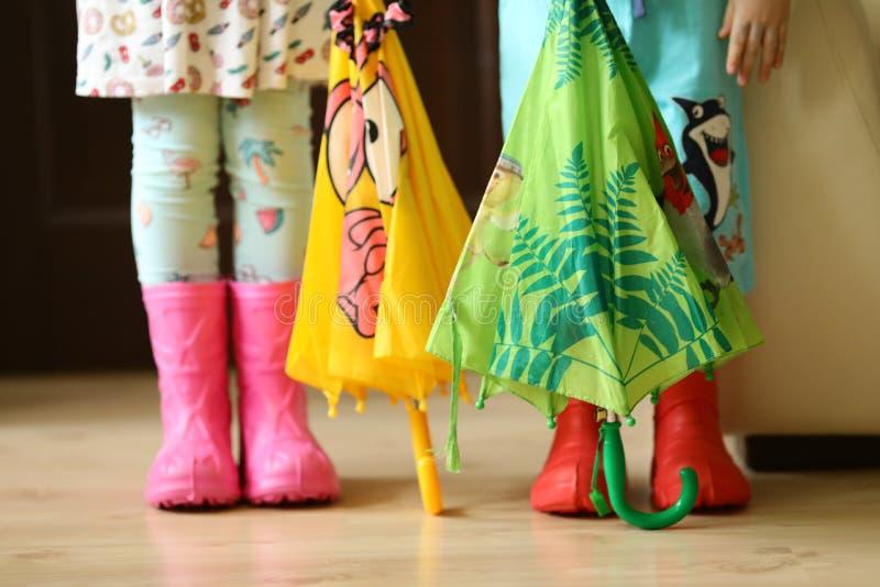 Niños en el desgaste colorido de los rainboots bastante fresco y los paraguas fotos de archivo