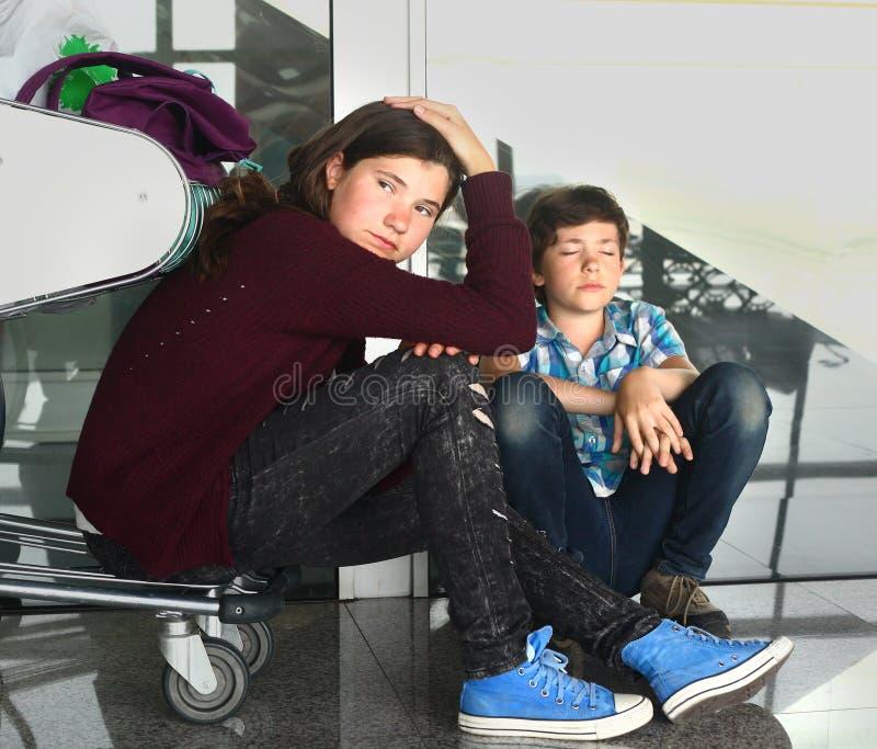 Niños en el fligt retrasado que espera triste del aeropuerto para fotos de archivo libres de regalías