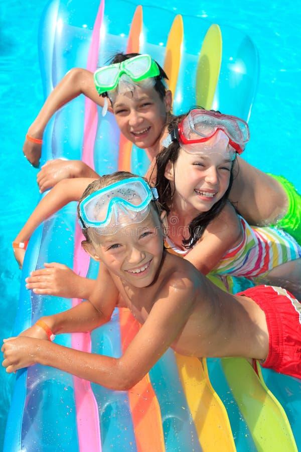 Niños en el flotador en piscina imagen de archivo libre de regalías