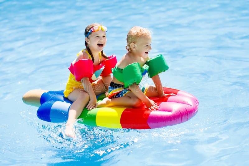 Niños en el flotador inflable en piscina fotos de archivo