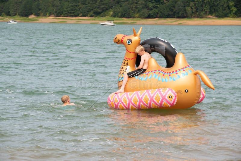 Niños en el juguete inflable en el lago foto de archivo