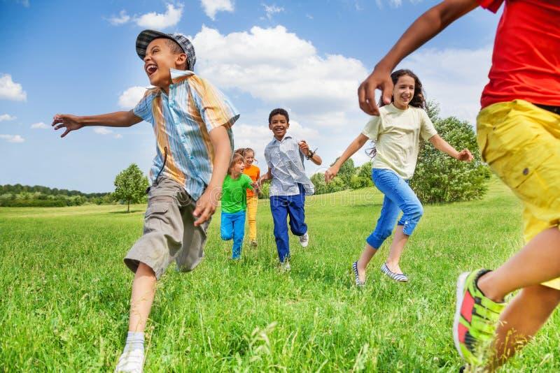 Niños en el movimiento del funcionamiento en campo verde imagenes de archivo