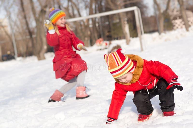 Niños en el parque del invierno que juega bolas de nieve imagen de archivo