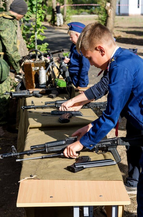 Niños en estudiantes uniformes de las clases del cadete competir en el desmontaje y el montaje del Kalashnikov foto de archivo libre de regalías