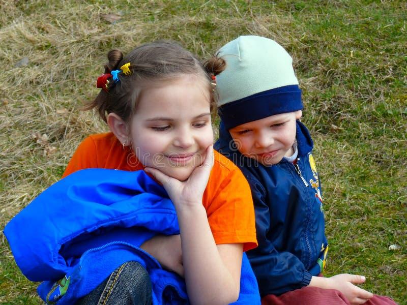 Niños en hierba fotos de archivo