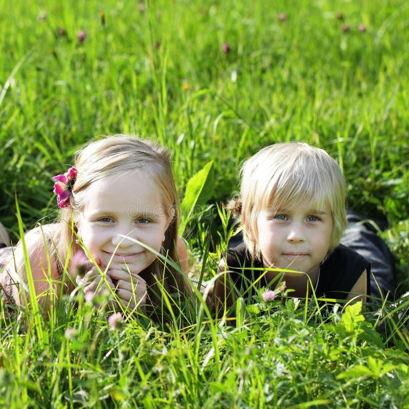 Niños en hierba del verano imagenes de archivo