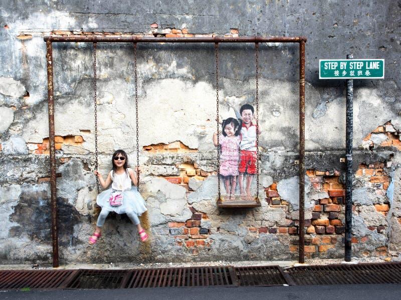 Niños en la calle Art Piece del oscilación en Georgetown, Penang, mA foto de archivo