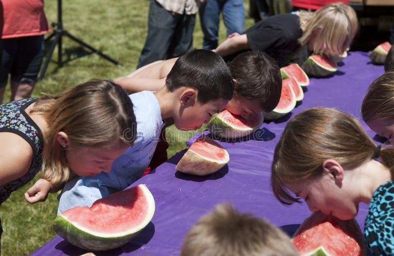 Niños en la competencia de la consumición de la sandía. imagen de archivo