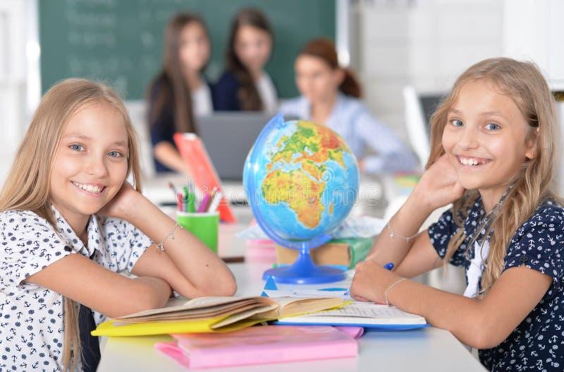 Niños en la escuela en lecciones imagen de archivo