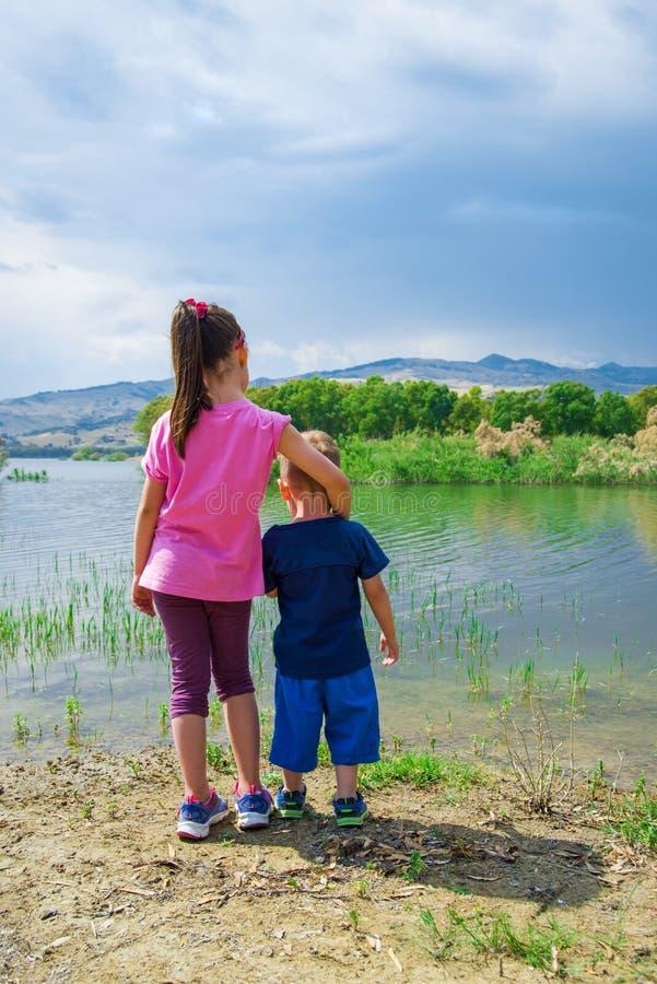 Niños en la orilla del lago Pozzillo, Sicilia foto de archivo