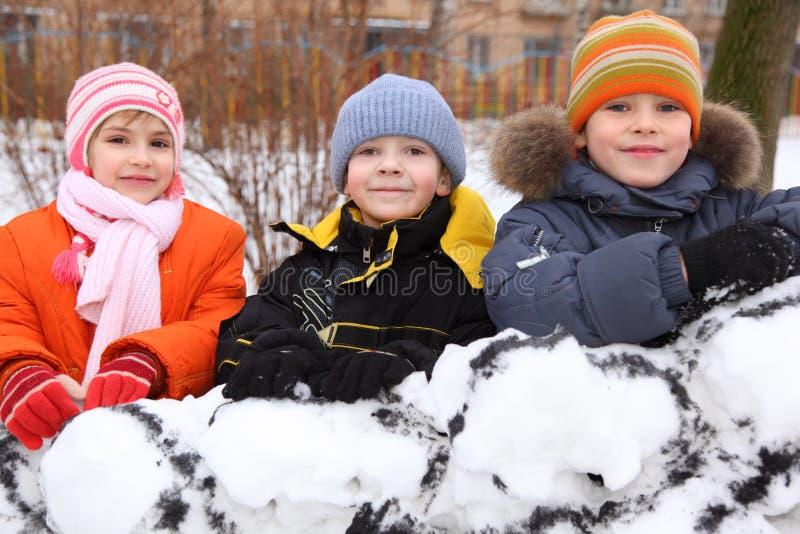 Niños en la pared de la fortaleza de la nieve en yarda fotografía de archivo libre de regalías