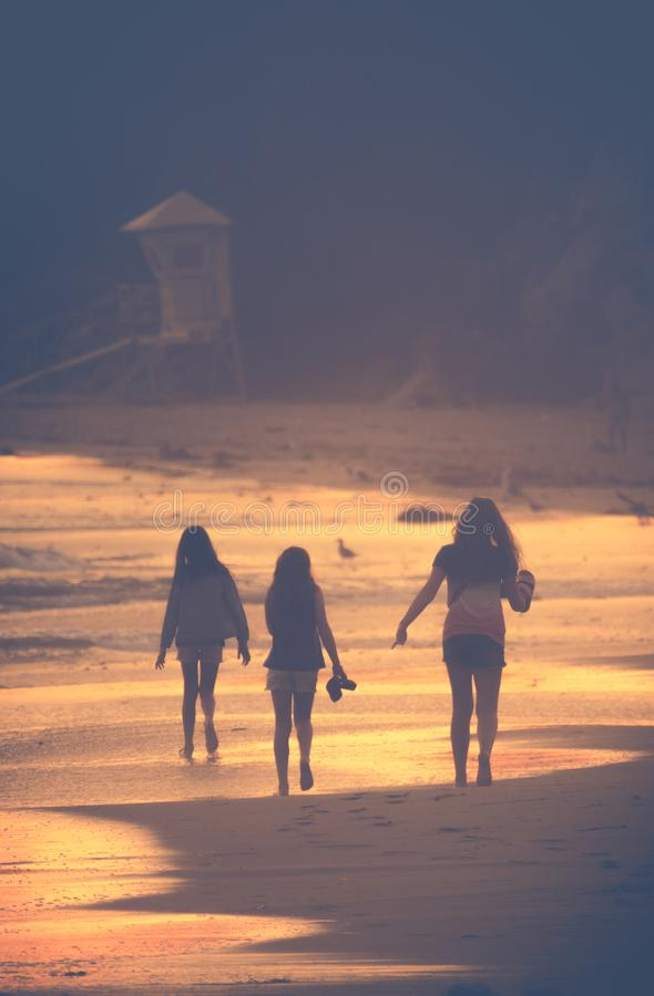 Niños en la playa de oro de la puesta del sol imagen de archivo