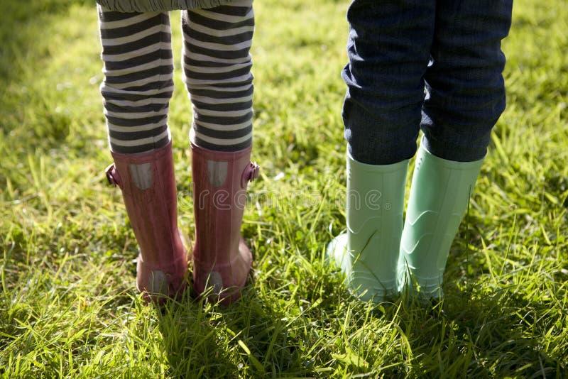 Niños en las botas de Wellington que se colocan en hierba fotos de archivo libres de regalías