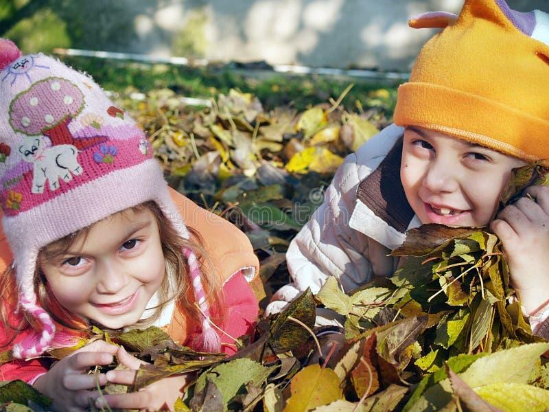 Niños en las hojas foto de archivo