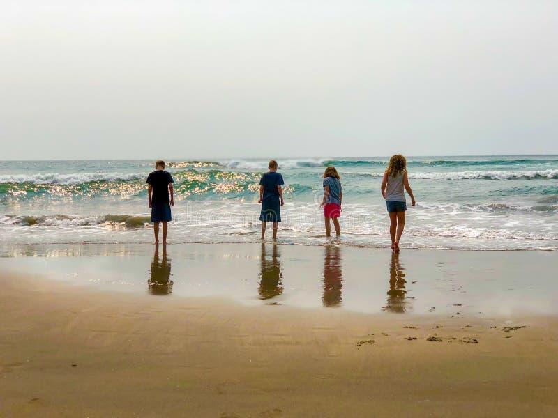 Niños en las ondas de observación de la playa imágenes de archivo libres de regalías