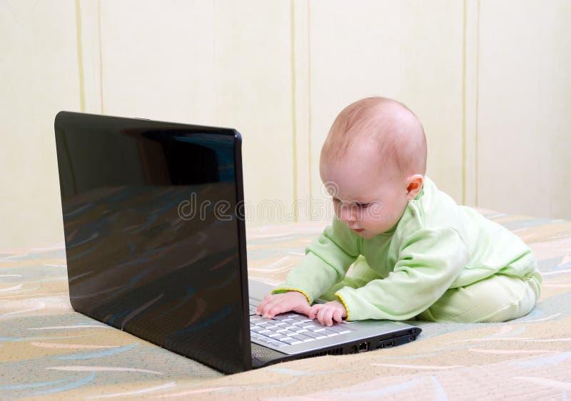 Niños en los pañales que juegan con un ordenador portátil imagen de archivo