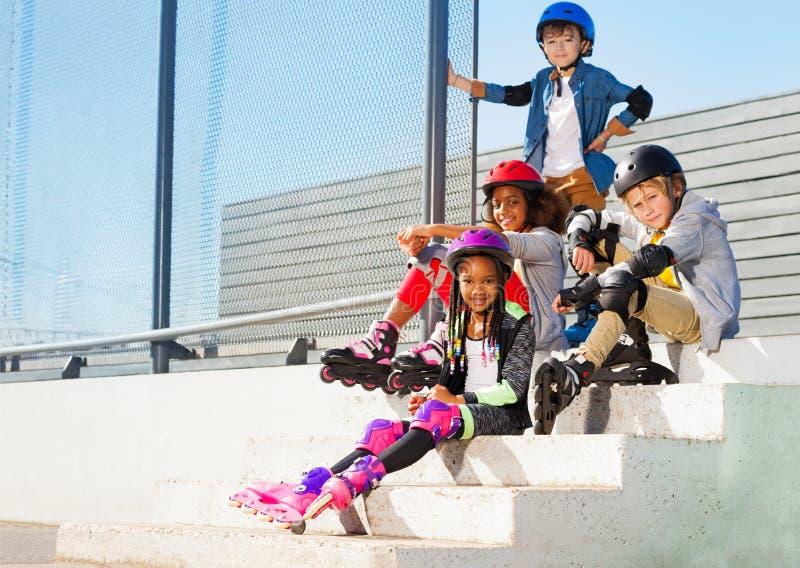 Niños en los pcteres de ruedas que se sientan en pasos del estadio foto de archivo libre de regalías
