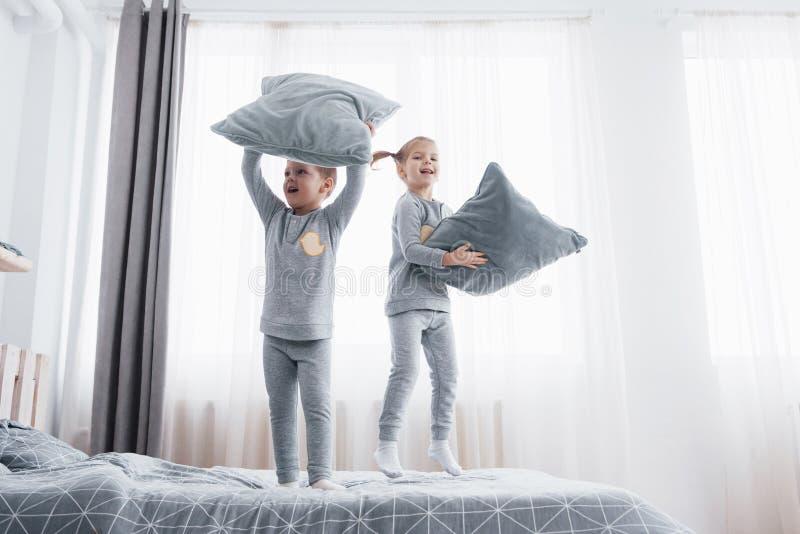 Niños en los pijamas calientes suaves que juegan en cama imagen de archivo