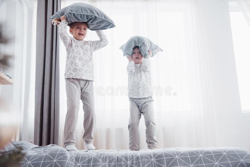 Niños en los pijamas calientes suaves que juegan en cama fotografía de archivo