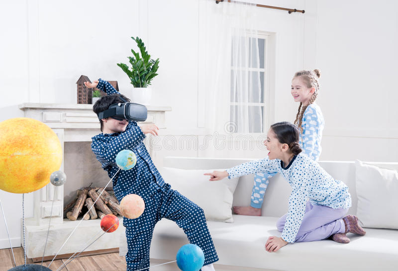 Niños en los pijamas que juegan con las auriculares de la realidad virtual en casa foto de archivo