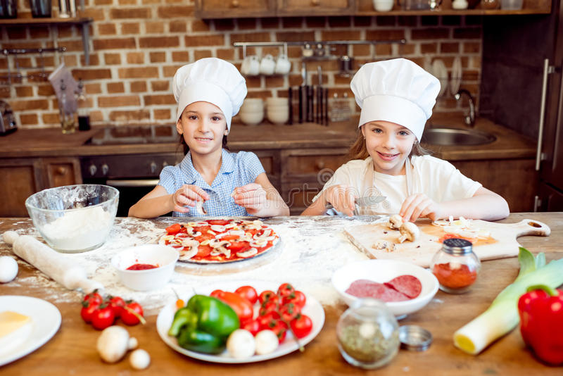 Niños en los sombreros del cocinero que hacen la pizza fotografía de archivo libre de regalías