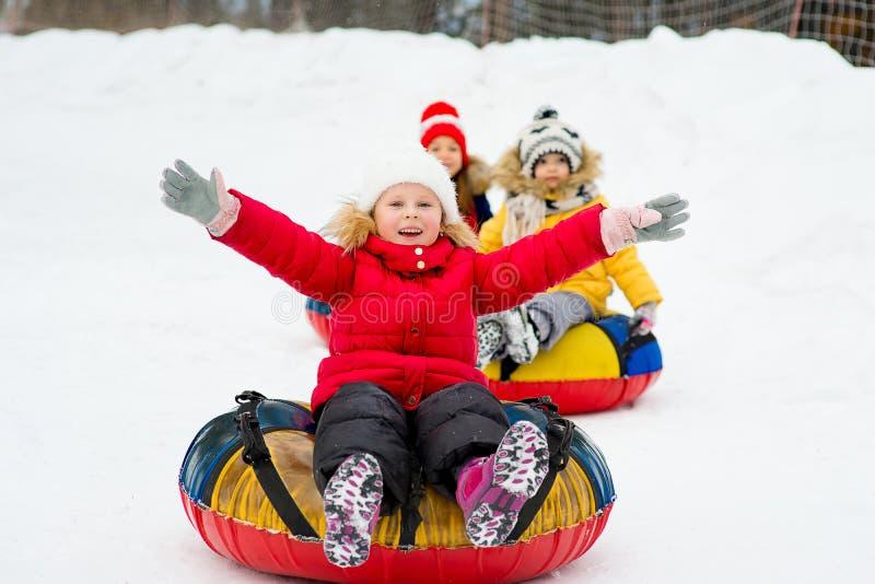 Niños en los tubos de la nieve cuesta abajo en el día de invierno fotos de archivo