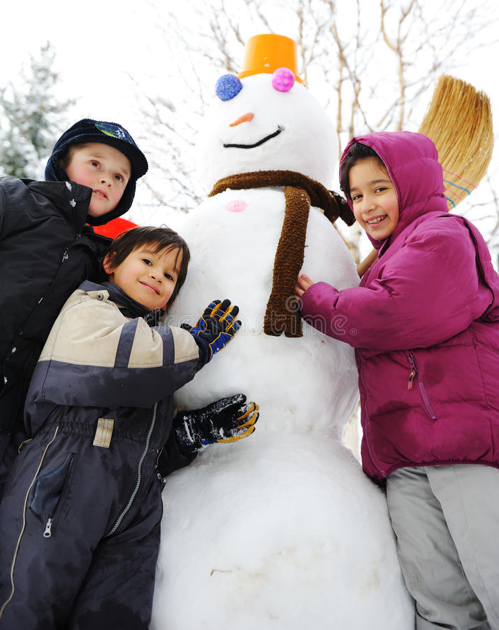 Niños en nieve con el muñeco de nieve fotografía de archivo