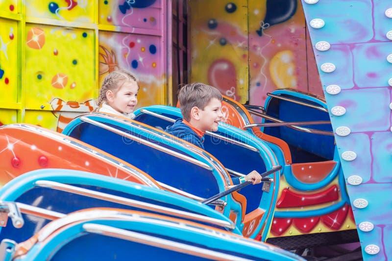 Niños en parque de atracciones imagen de archivo