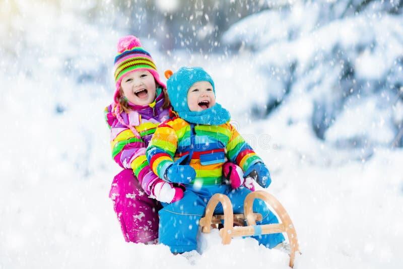 Niños en paseo del trineo Estrellazo a través de la nieve Diversión de la nieve del invierno imagenes de archivo