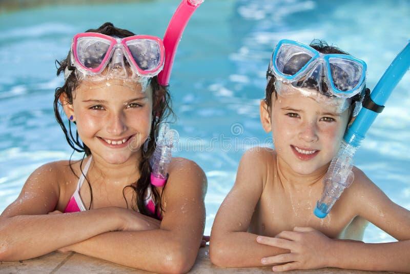 Niños en piscina con los anteojos y el tubo respirador fotografía de archivo