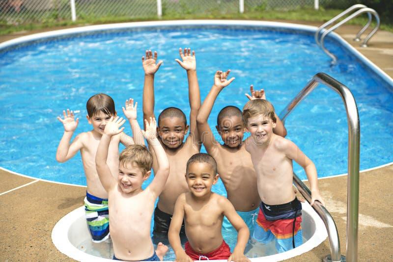 Niños en piscina exterior foto de archivo libre de regalías