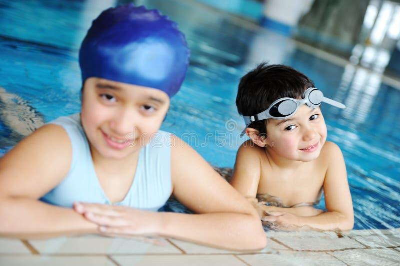 Niños en piscina que aprenden la natación. imagenes de archivo