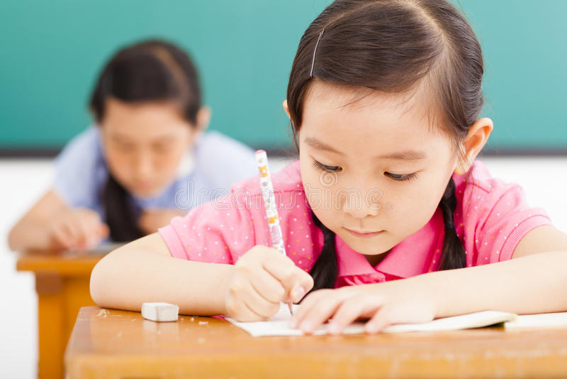 Niños en sala de clase con la pluma a disposición imagenes de archivo
