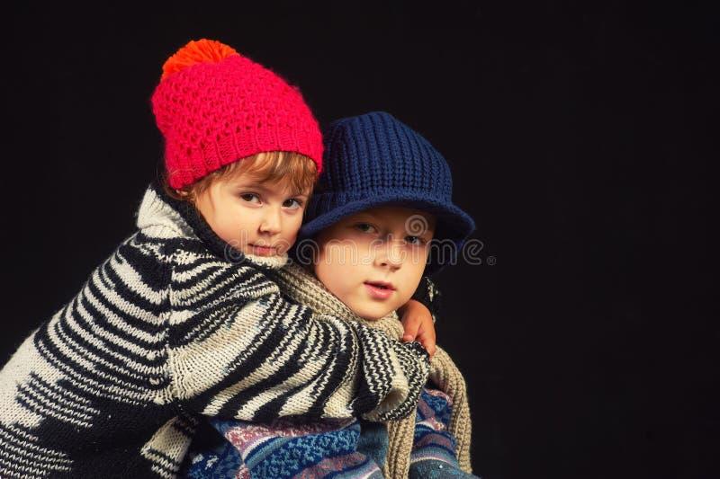 Niños en sombreros y suéteres hechos punto calientes en un fondo oscuro fotos de archivo libres de regalías
