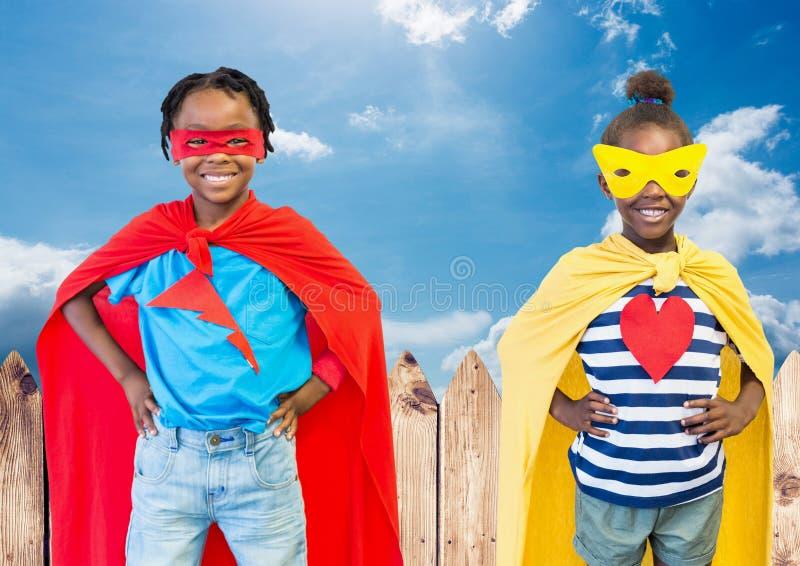 Niños en traje del super héroe con las manos en su cintura que se opone al cielo en fondo fotos de archivo