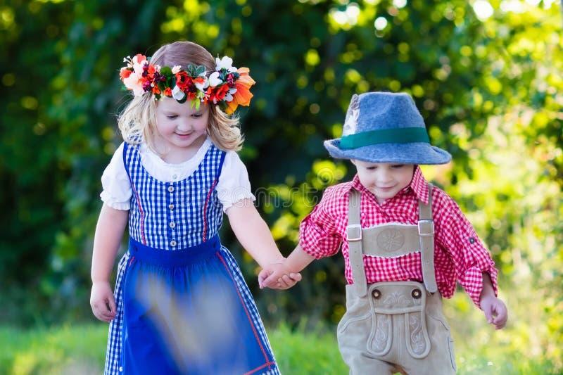 Niños en trajes bávaros en campo de trigo imagenes de archivo