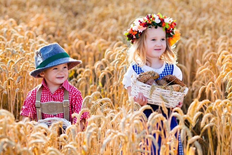 Niños en trajes bávaros en campo de trigo imagen de archivo libre de regalías