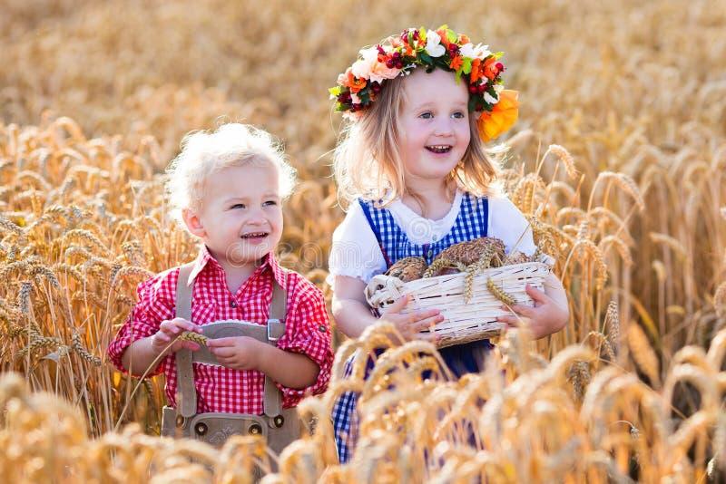 Niños en trajes bávaros en campo de trigo foto de archivo