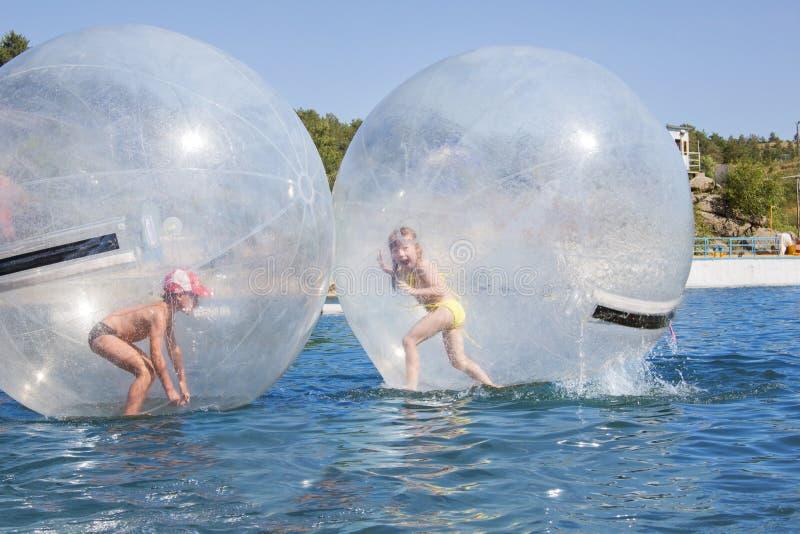 Niños en un globo que flota en el agua. fotografía de archivo libre de regalías