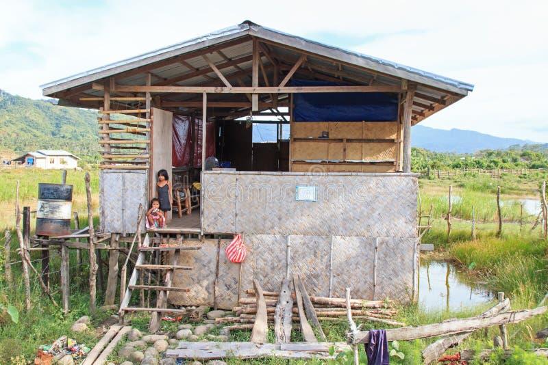 Niños en un hogar tradicional en el pequeño pueblo de Nacpan en las Filipinas Estos hogares se hacen de bambúes imagenes de archivo