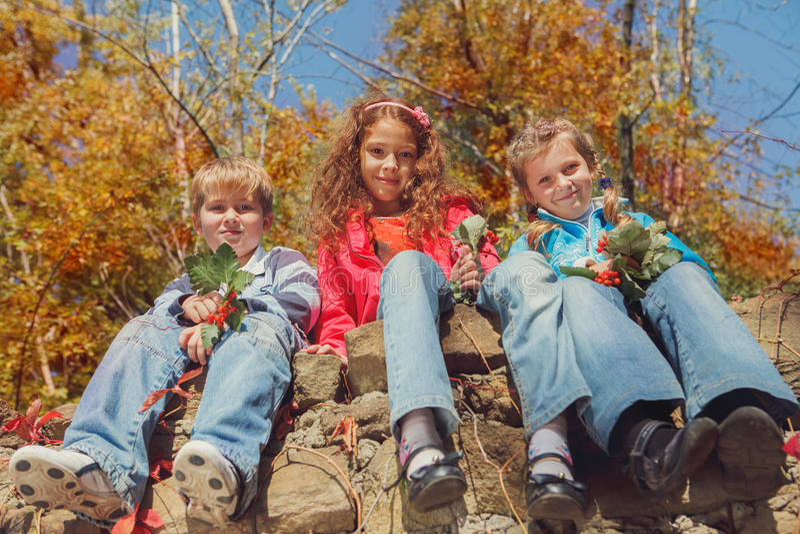 Niños en un jardín del otoño imagenes de archivo