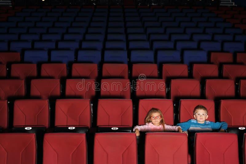 Niños en un pasillo vacío del cine imagen de archivo