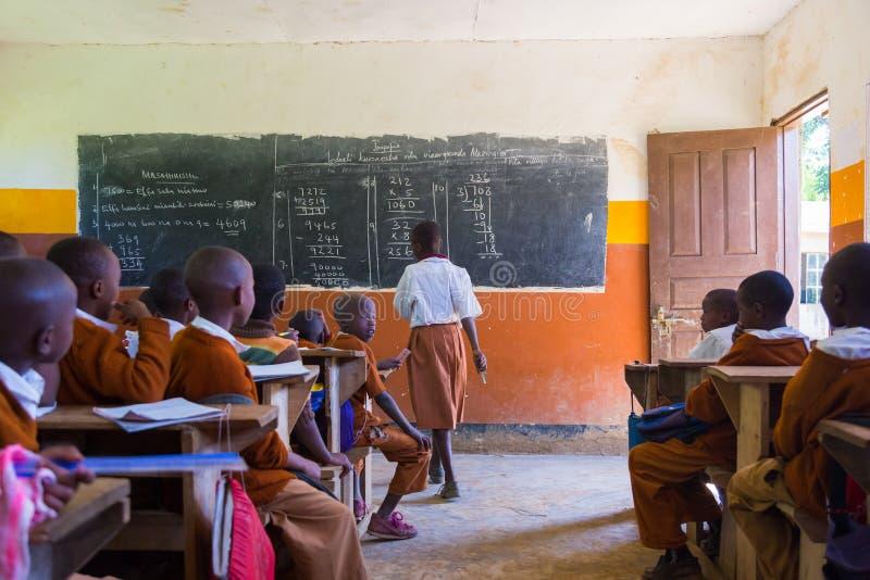 Niños en uniformes en la sala de clase de la escuela primaria listetning al profesor en zona rural cerca de Arusha, Tanzania, Áfr imagenes de archivo